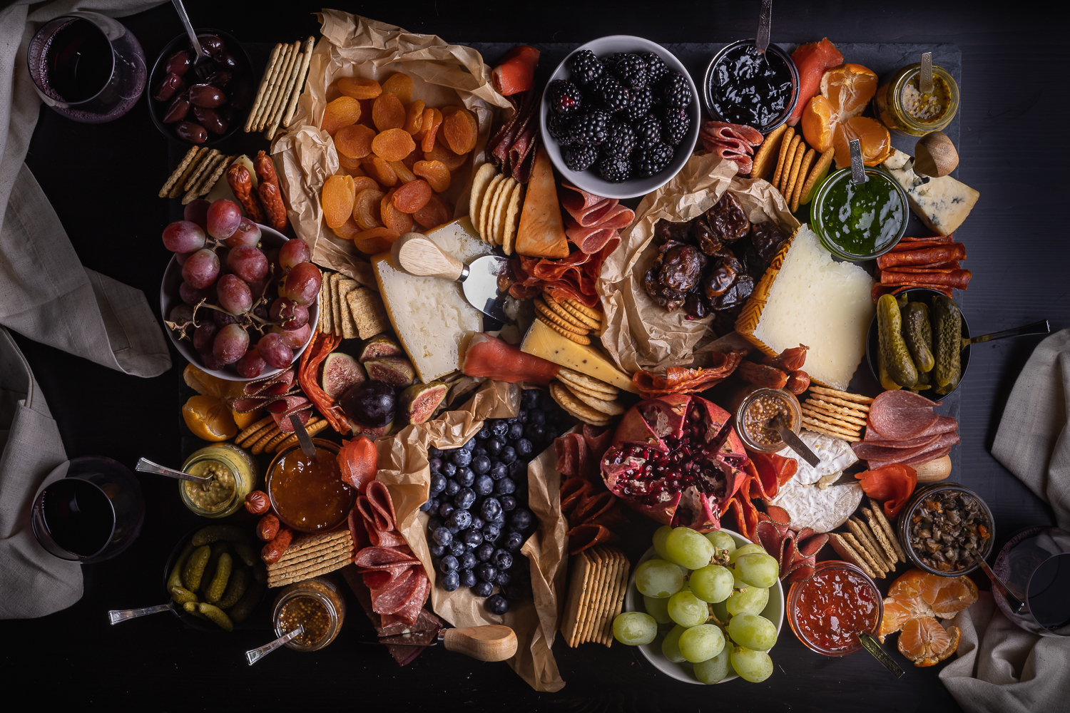 charcuterie board by Jules Sherred with fruits, crackers, meats, cheeses, pickles, and jams.