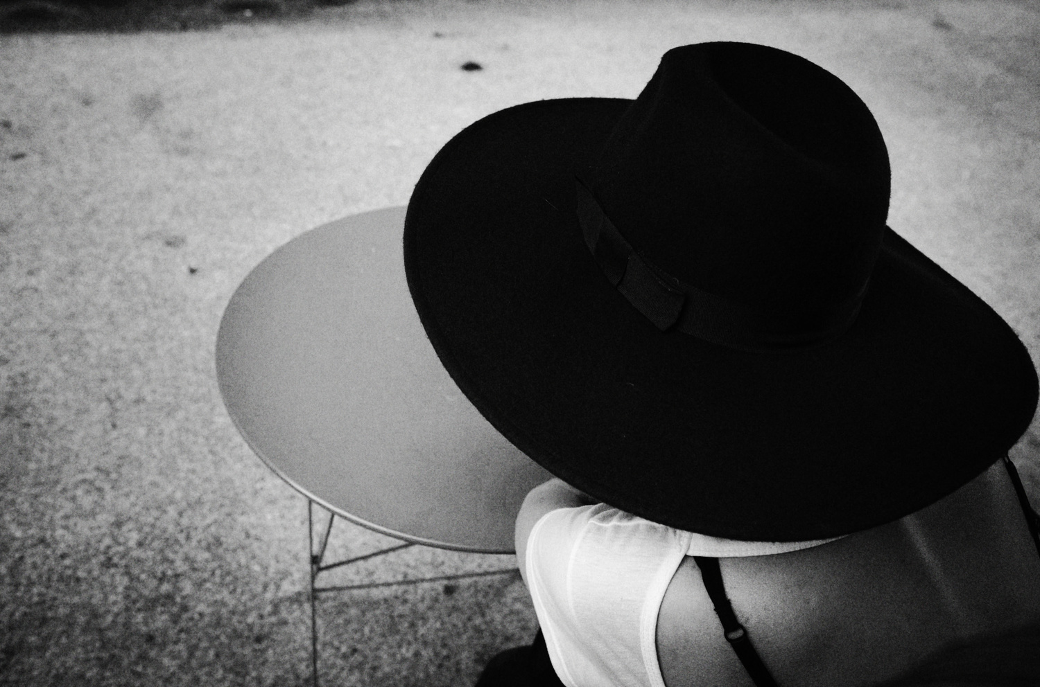 A woman s dark blue hat (here in dark black) becomes a key element in the  interplay between her and the table at which she sits. 26b7c62829a