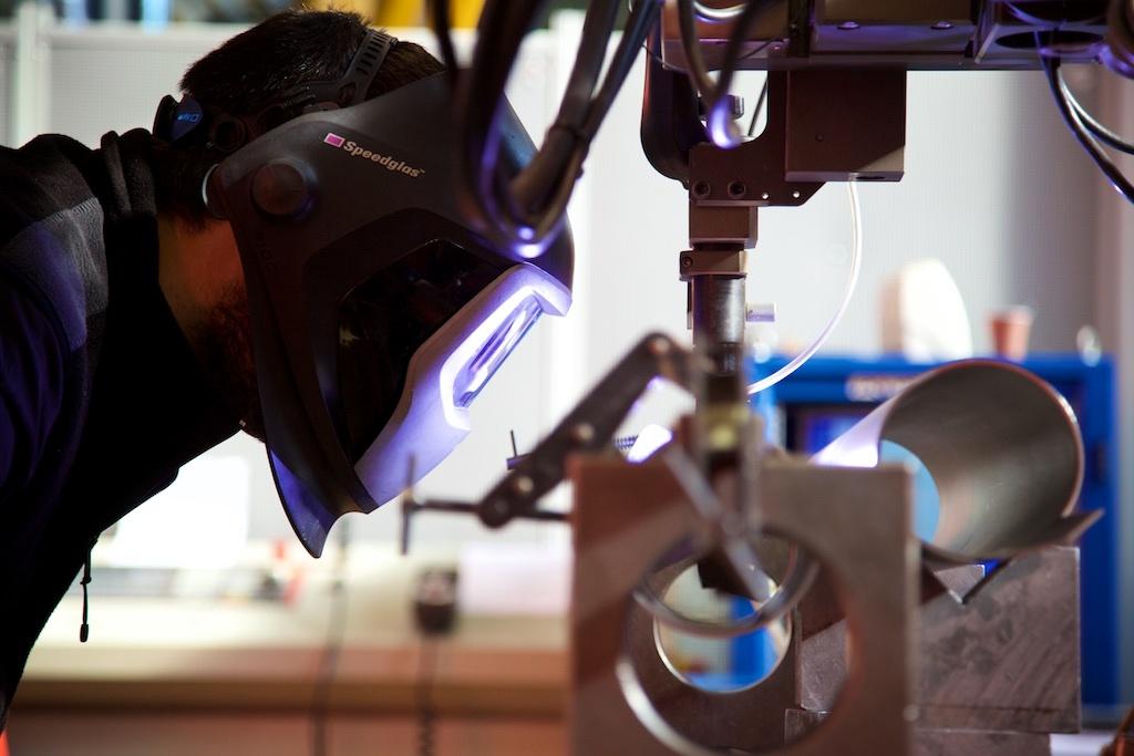 A welder checks the work done by a welding robot at CERN - Photo by Ruben Lammerink