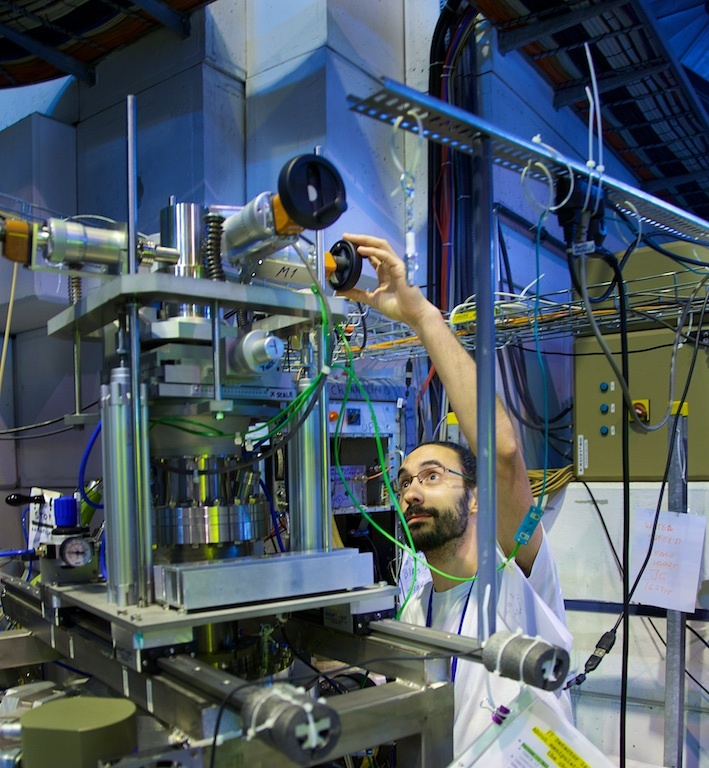 A scientist calibrates an experiment at ISOLDE - Photo by Ruben Lammerink