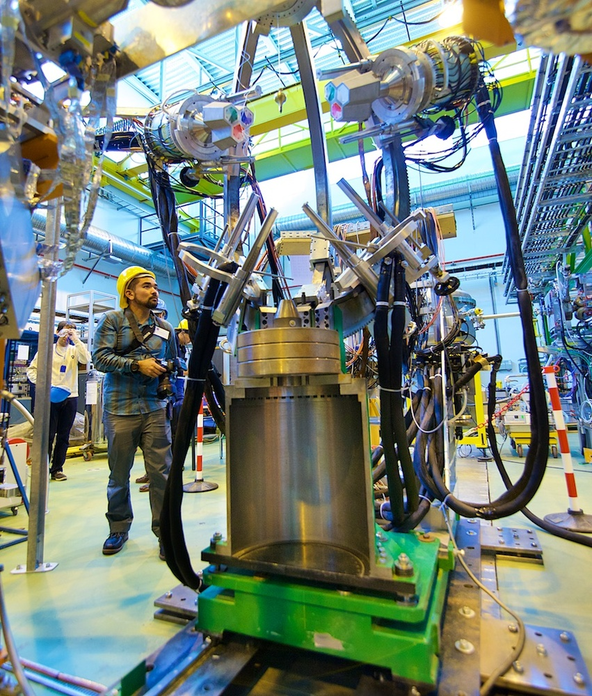 Photowalk attendee Andrew Hara stands beside the heart of an ISOLDE experiment - Photo by Ruben Lammerink
