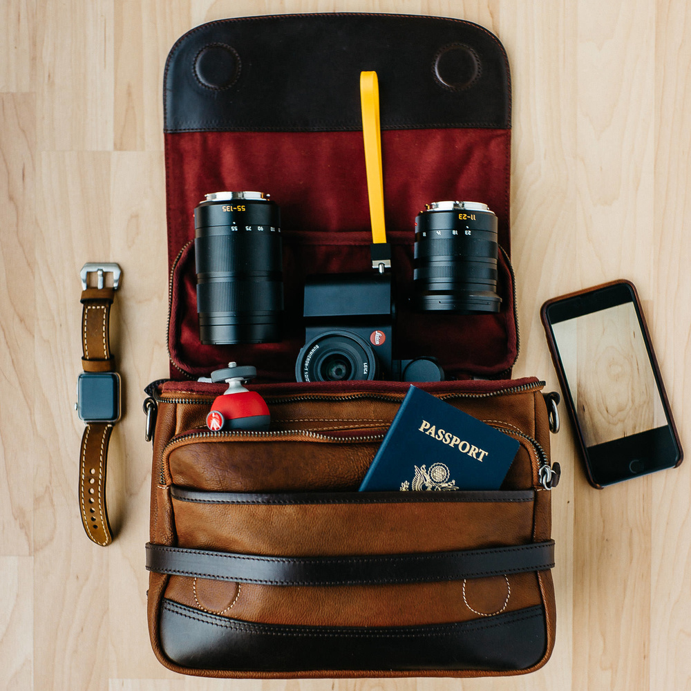 Photo of Leica T Mirrorless Camera with travel essentials in a Wotancraft Ryker bag