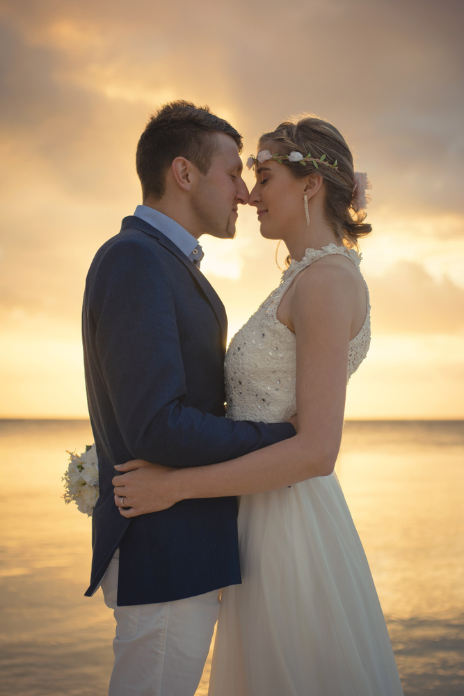 Sunset wedding with couple on beach by the sea