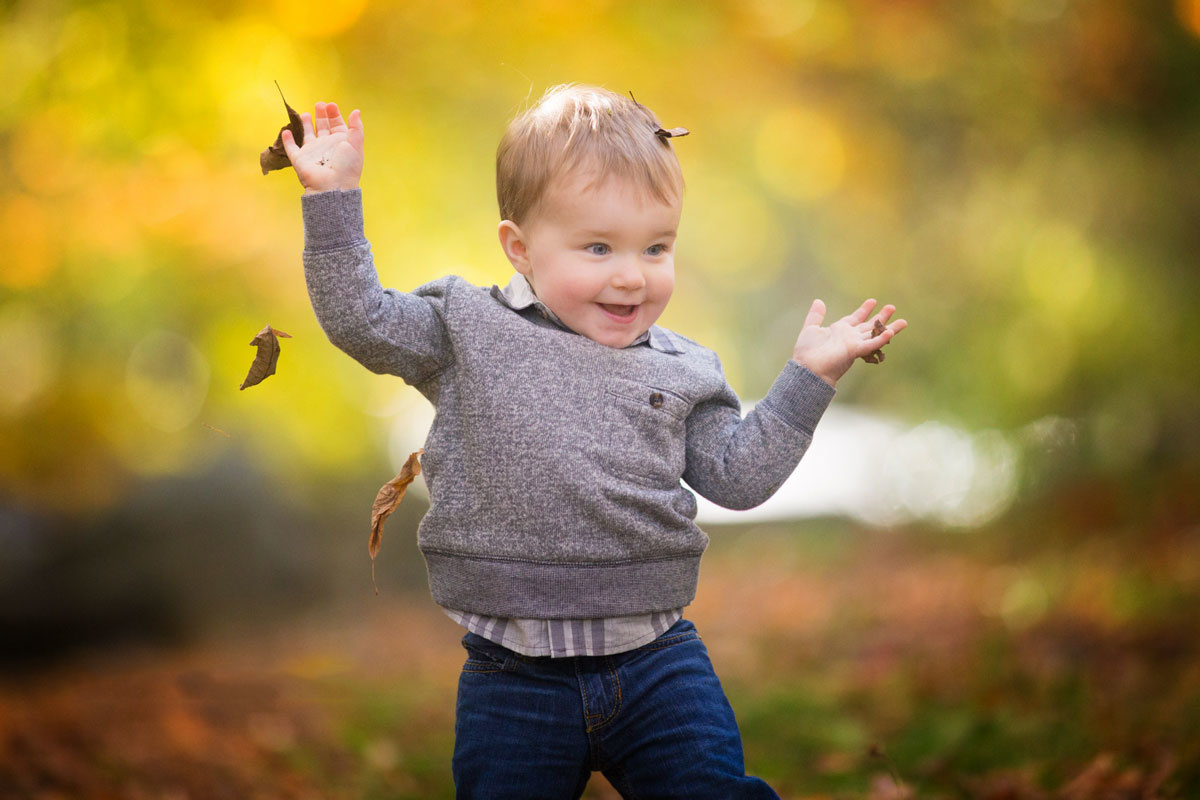 happy boy tossing leaves in the fall