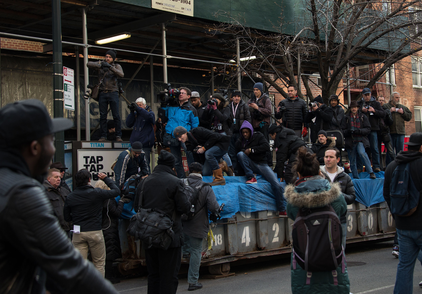 News photographers gain some height by standing on a dumpster on Saturday, Dec. 13, 2014 at the Millions March NYC. With the layoffs of so many photojournalists, there will be less eyes on key moments in New York City. Photo by Chelsea Katz.