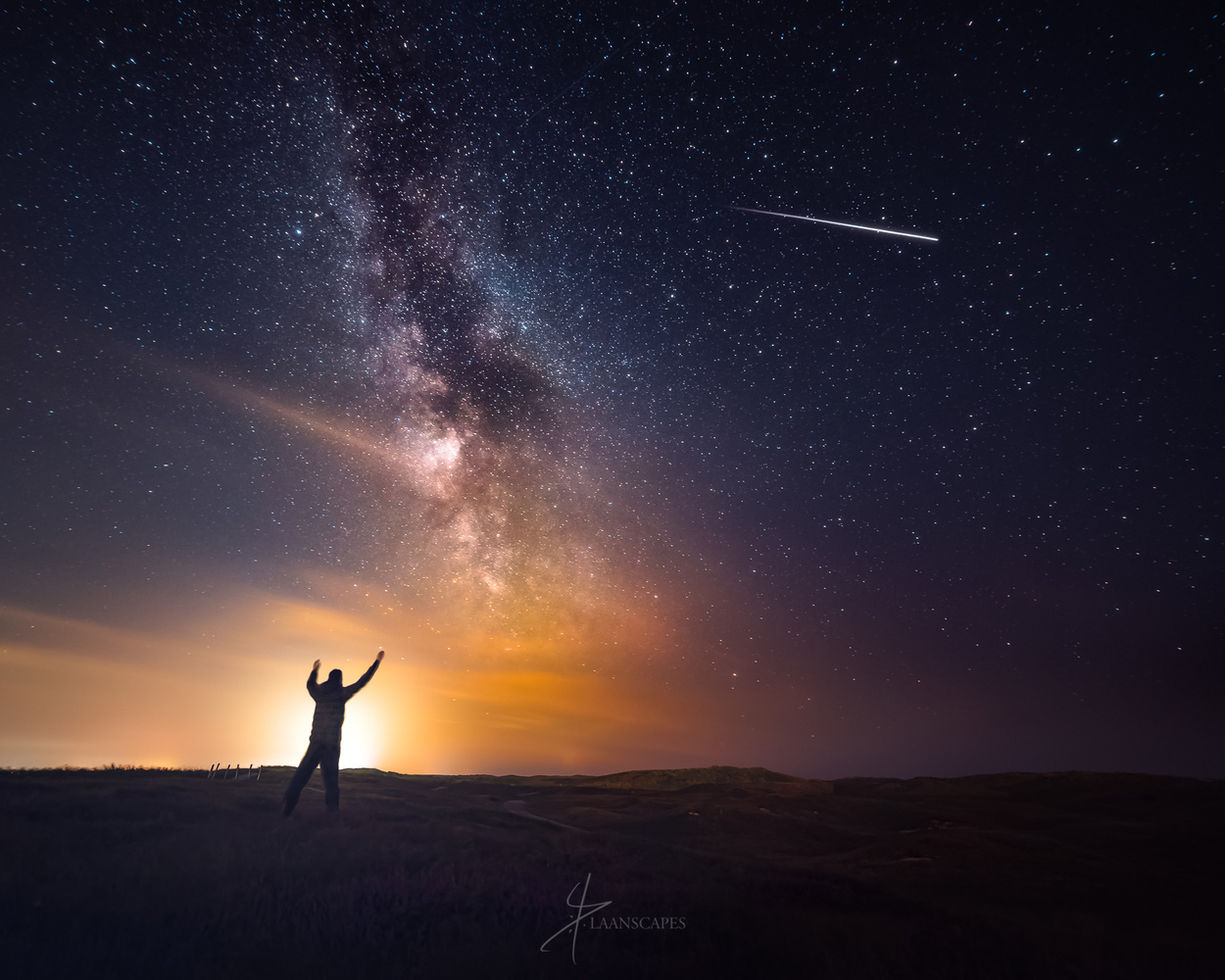 Photograph of a man greeting the International Space Station with the Milky Way overhead.