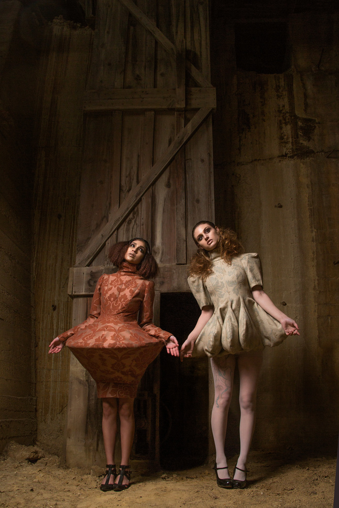 two models in couture dresses in a gold mine