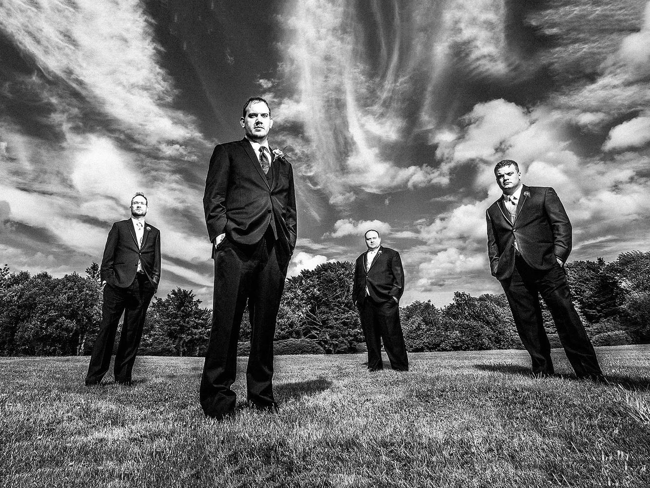 four groomsmen standing in field
