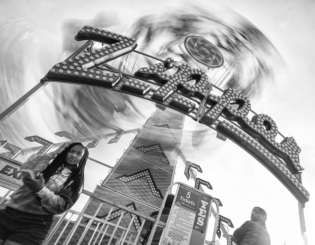 Using the continuous shooting mode with a slow shutter speed caught this moment between the ride operator and the woman in the foreground, with the ride spinning around behind them.