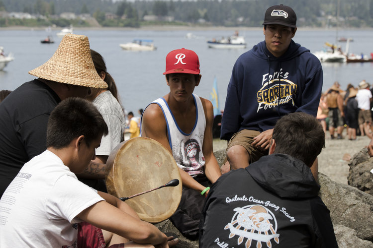 A group of young men singing traditional songs together beside the water. Photo by Gabrielle Colton.