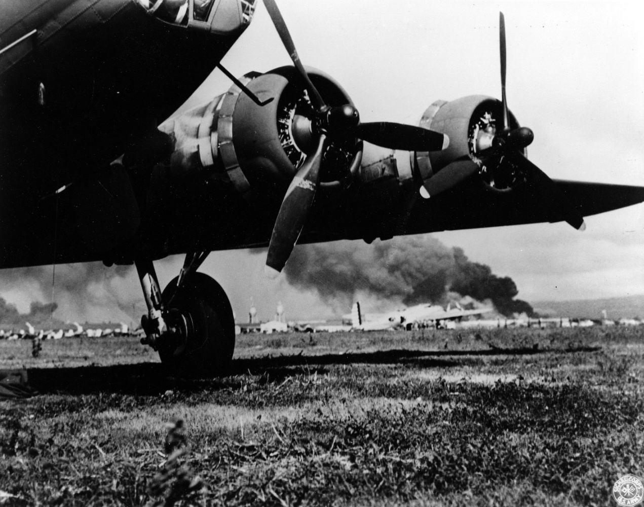 """A U.S. Army B-17E at Hickam Air Field, after landing safely during the Japanese air raid. Smoke from burning ships at Pearl Harbor is visible in the distance. Photographer may be Staff Sergeant Lee Embree."""