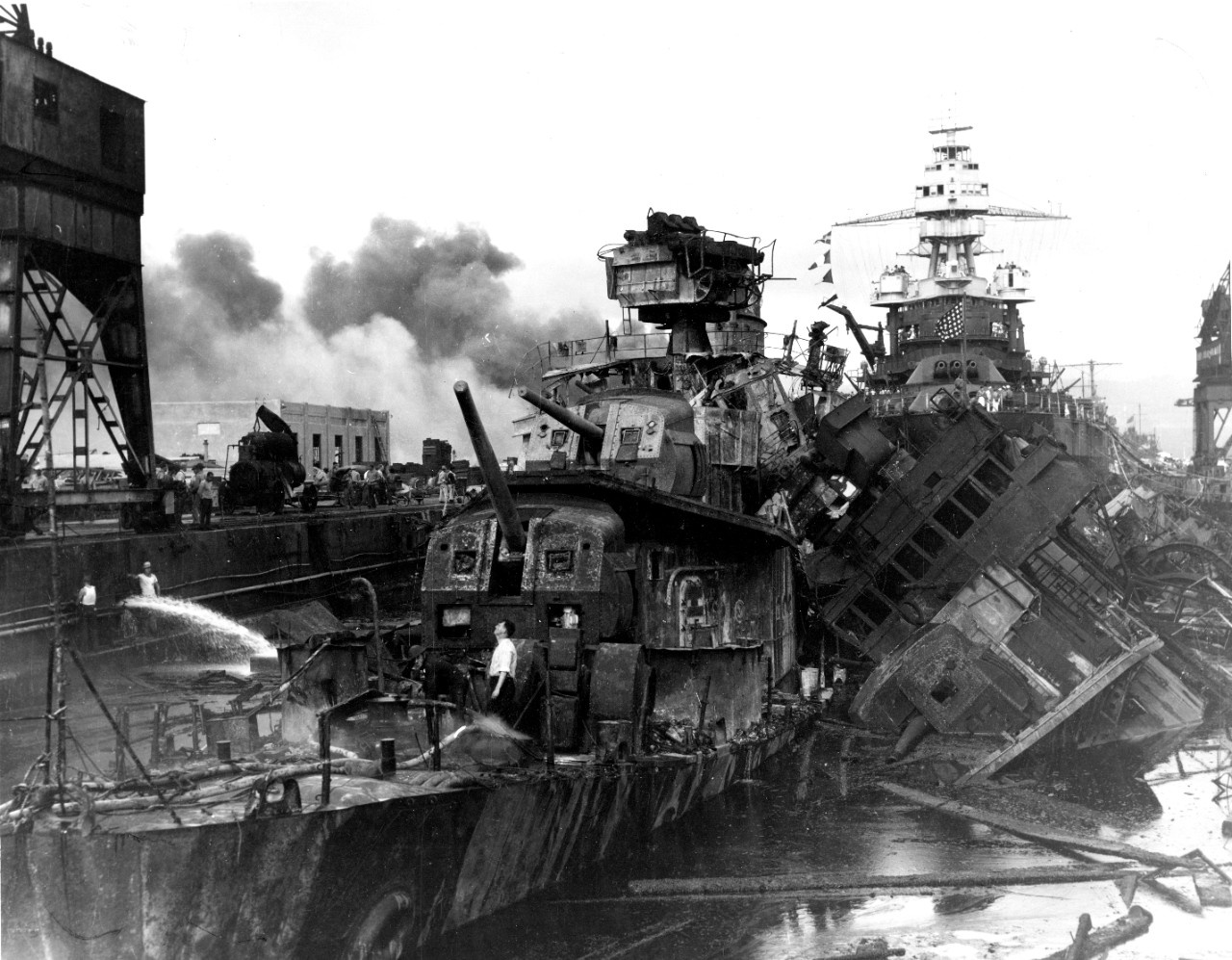 """USS Downes, at left, and USS Cassin, capsized at right, burned out and sunk in the Pearl Harbor Navy Yard drydock on 7 December 1941, after the Japanese attack. The relatively undamaged USS Pennsylvania is in the background."" Note the man in a white shir"