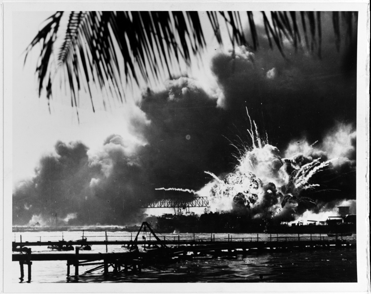 The forward magazine of USS Shaw (DD-373) explodes during the second Japanese attack wave. At right is the bow of USS Nevada (BB-36), with a tug alongside fighting fires. Photographed from Ford Island, with a dredging line in the foreground. U.S. Naval Hi
