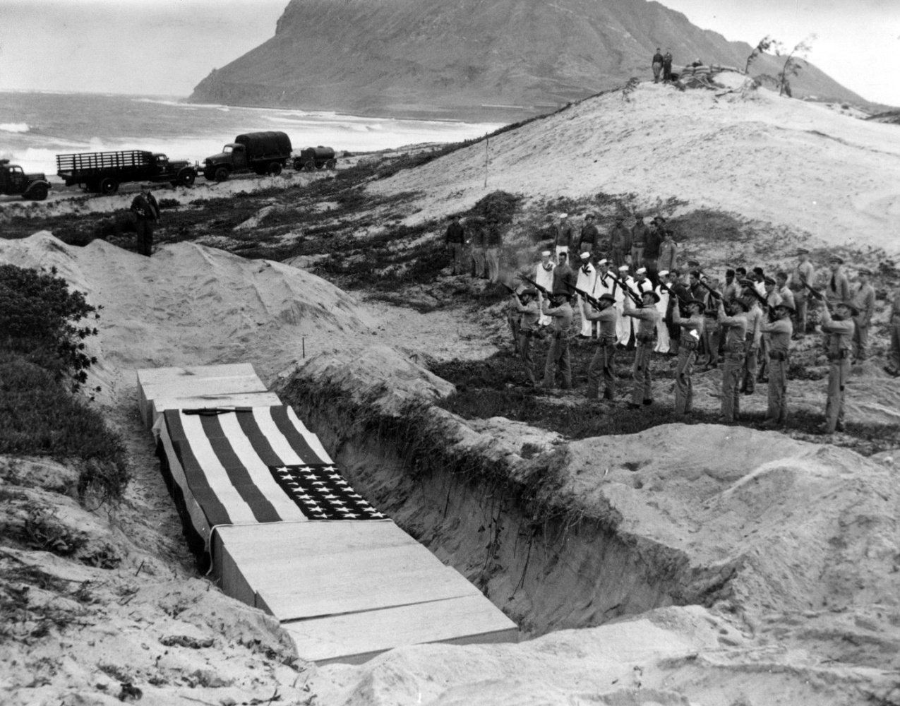 """A Marine rifle squad fires a volley over the bodies of fifteen officers and men killed at Naval Air Station Kaneohe Bay during the Pearl Harbor raid. These burial ceremonies took place on 8 December 1941, the day after the attack."""