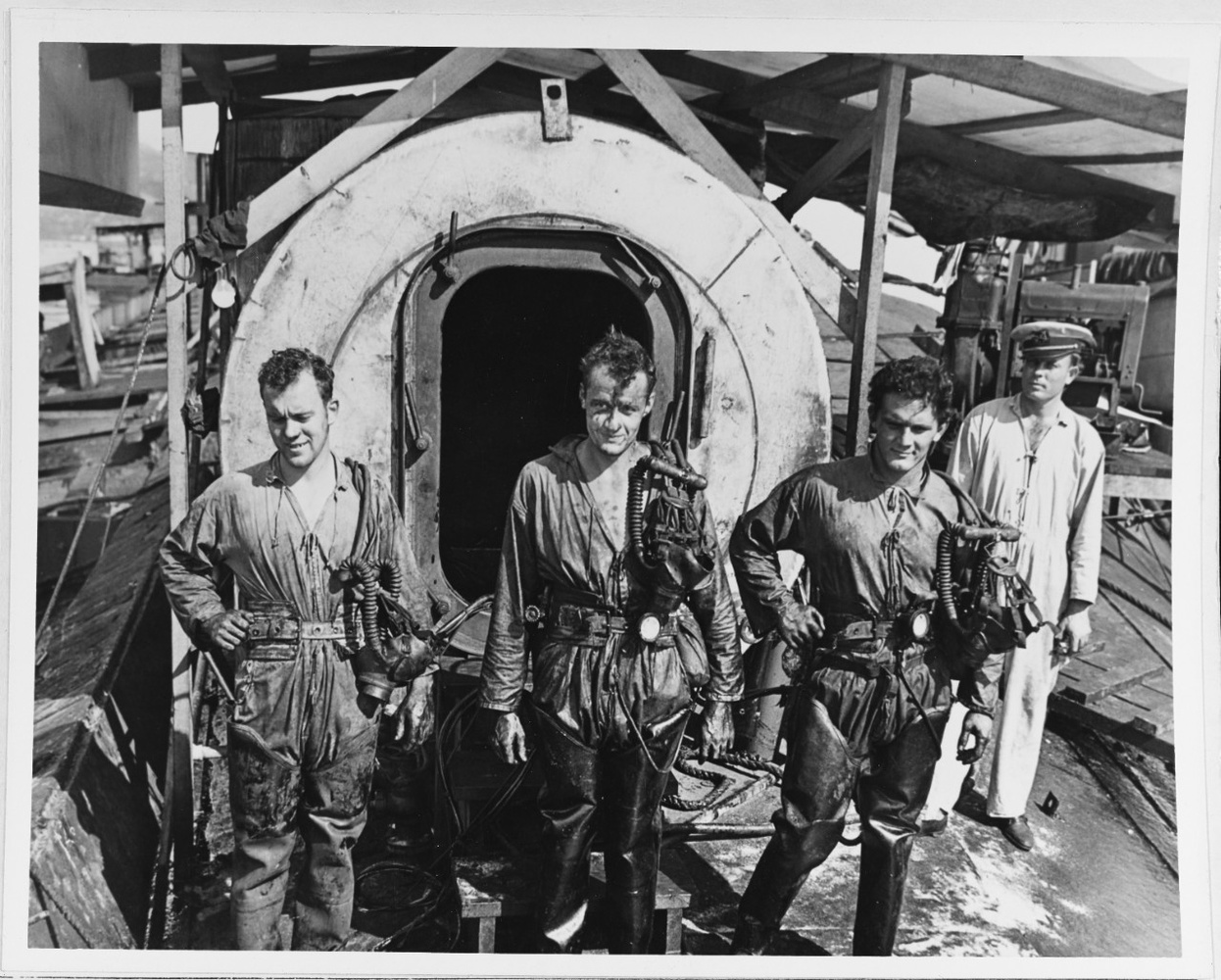 "Taking the time to pose during cleanup. ""Divers standing in front of a decompression chamber, while they were working to salvage ships sunk in the 7 December 1941 Japanese air raid on Pearl Harbor. Note warrant officer standing at right."""