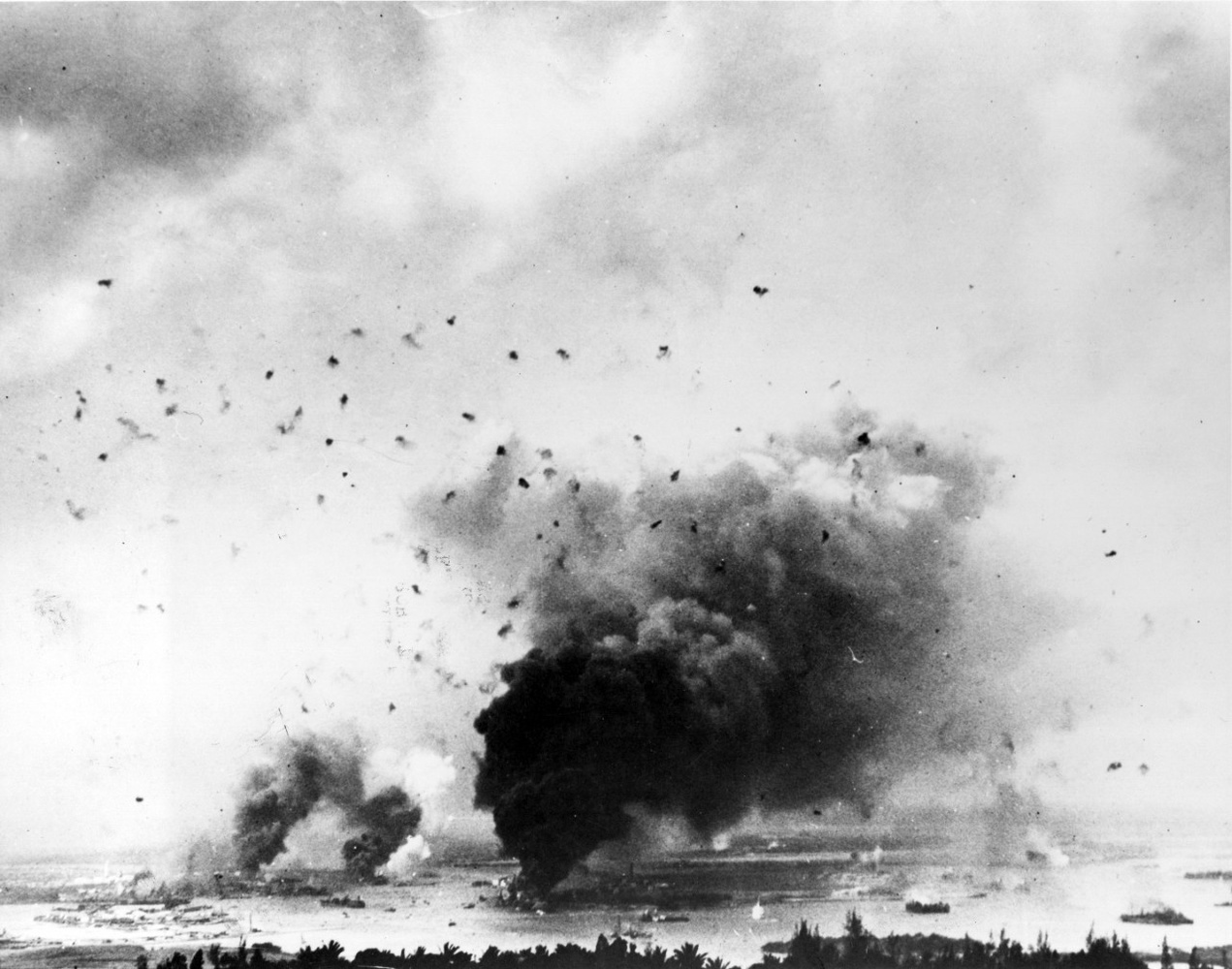A view of Pearl Harbor looking southwest from the hills towards the north. Taken during the Japanese raid, with anti-aircraft shell bursts overhead. Large column of smoke in lower center is from USS Arizona.