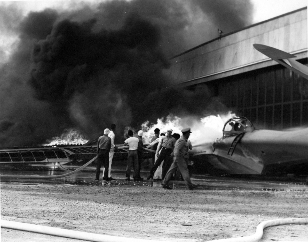 A patrol bomber burning at Naval Air Station Kaneohe, on Oahu, with crews trying to put out the fires.