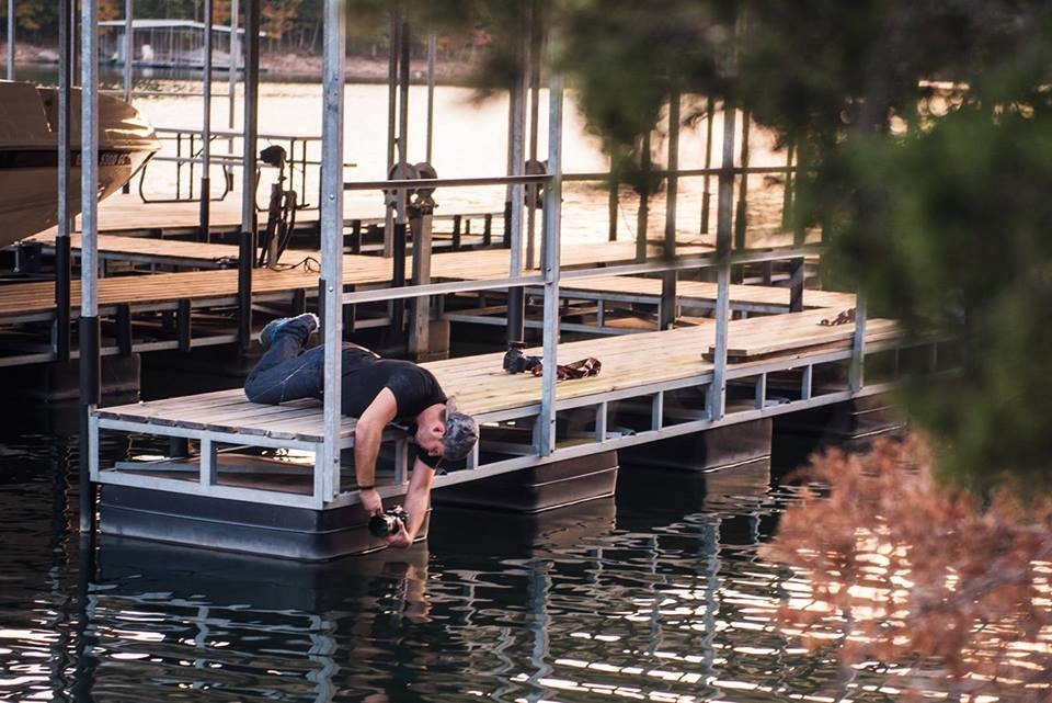 Behind the scenes of Jason Vinson hanging over water with his camera to get a low angle