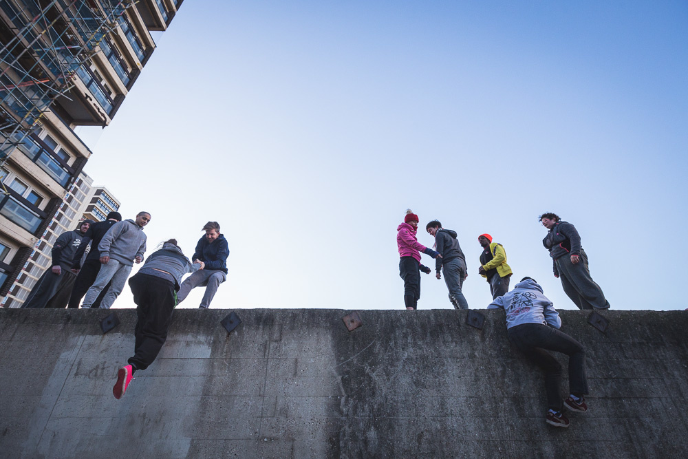 Parkour athletes gathering on the top of a wall. Andy Day.