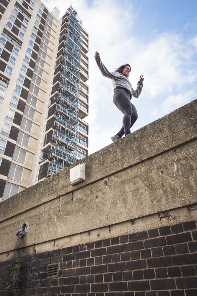 A female parkour athelte running along the top of a wall. Andy Day.