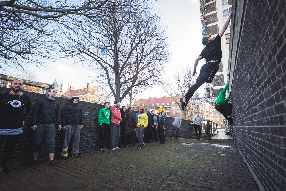 A parkour athlete jumping to grab the top of a wall. Andy Day.