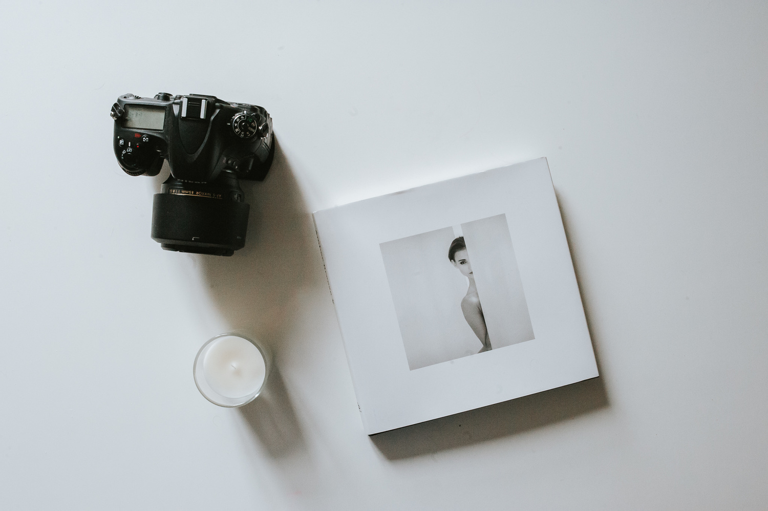 A digital camera, photography book and a candle placed on a white table.