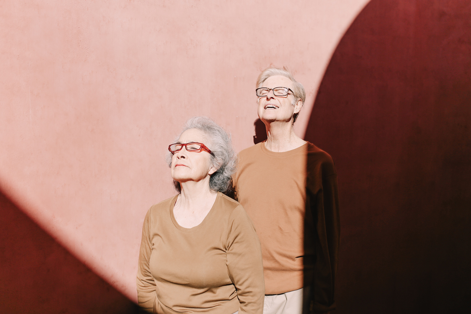 Elderly couple leaning against a wall.