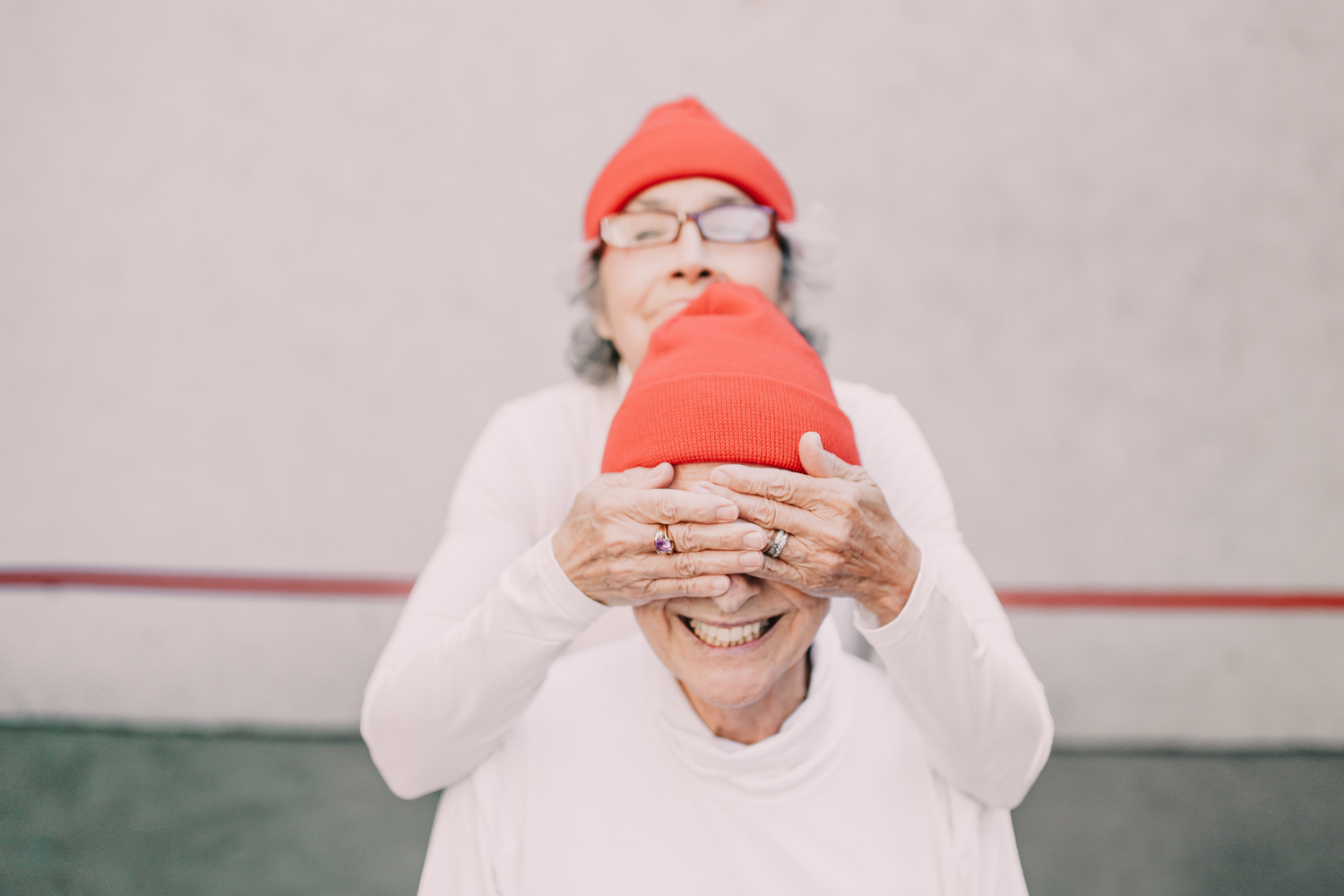 An elderly woman covering friend's face with her hands.
