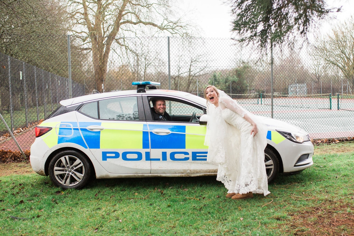 Bride posing with a police car.