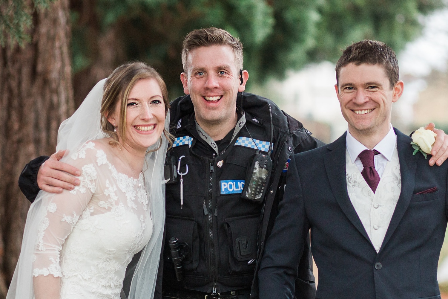Bride and groom posing with a policeman.
