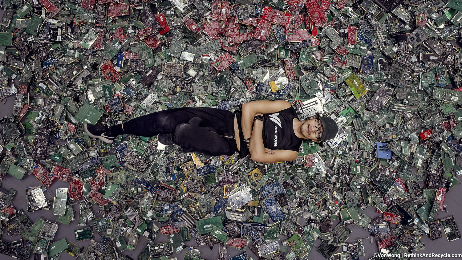 Image of Benjamin Von Wong posing on top of 4100 pounds of e-waste