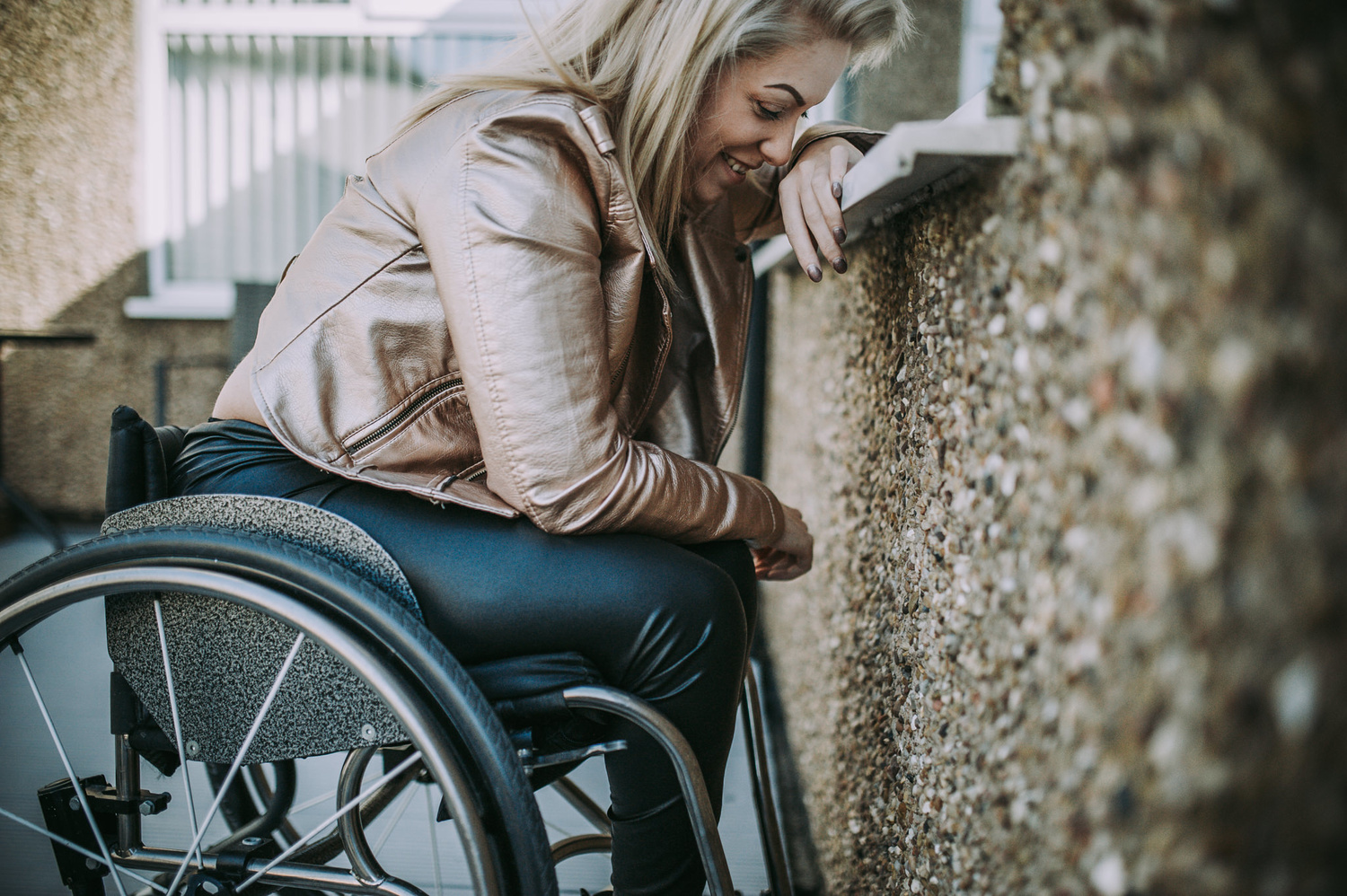 Young blond woman in a wheelchair, smiling