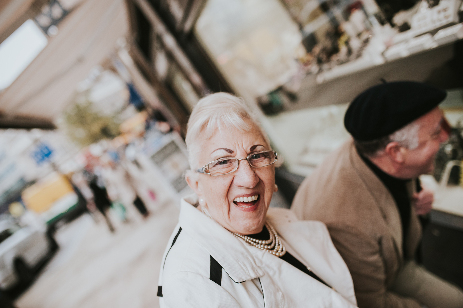An older woman with glasses, smiling.