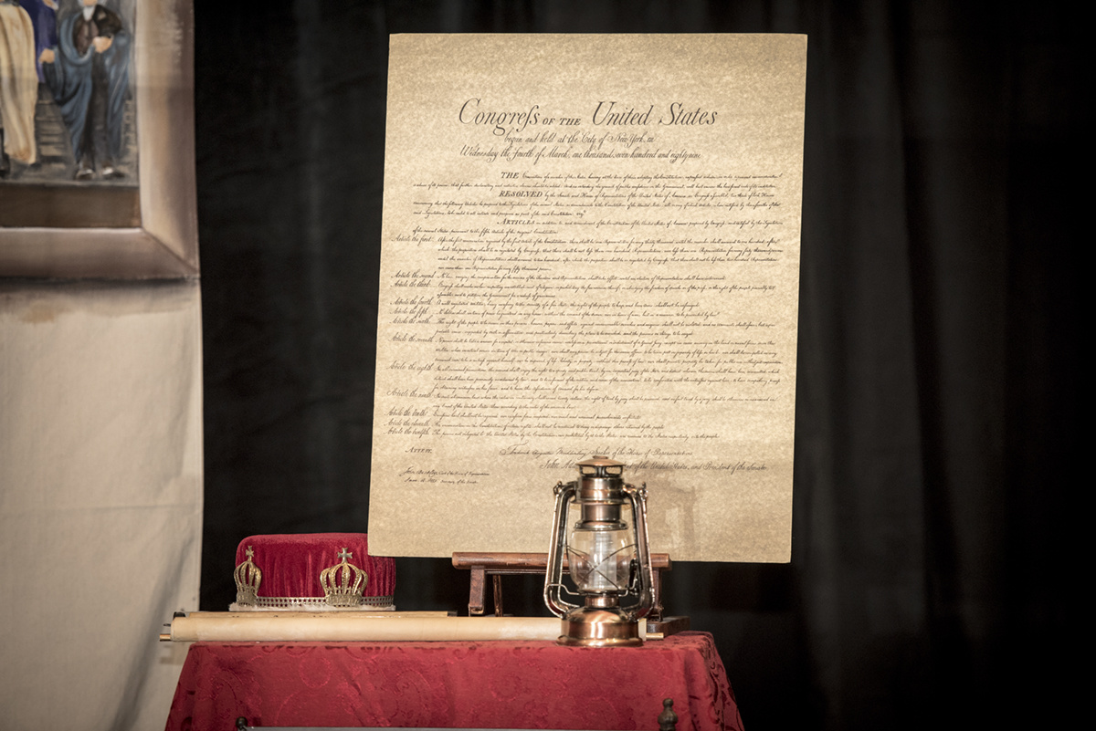 a photo of the US bill of rights next to a lantern on a table