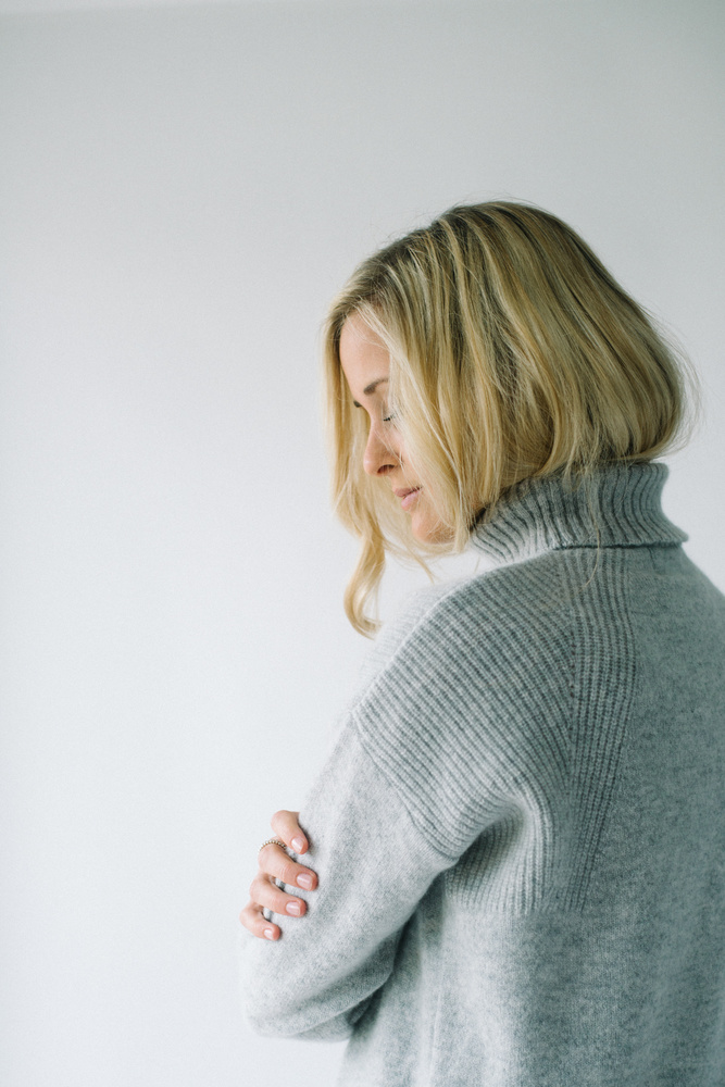 Blonde woman in a wooly jumper.