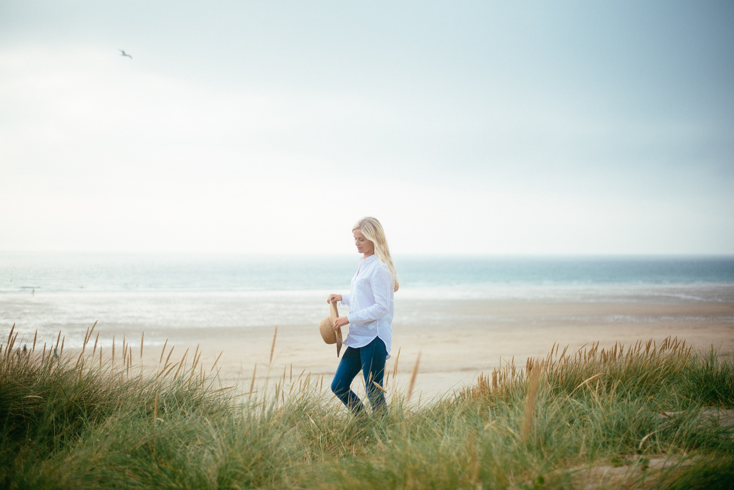 Young blonde woman walking by a beach.