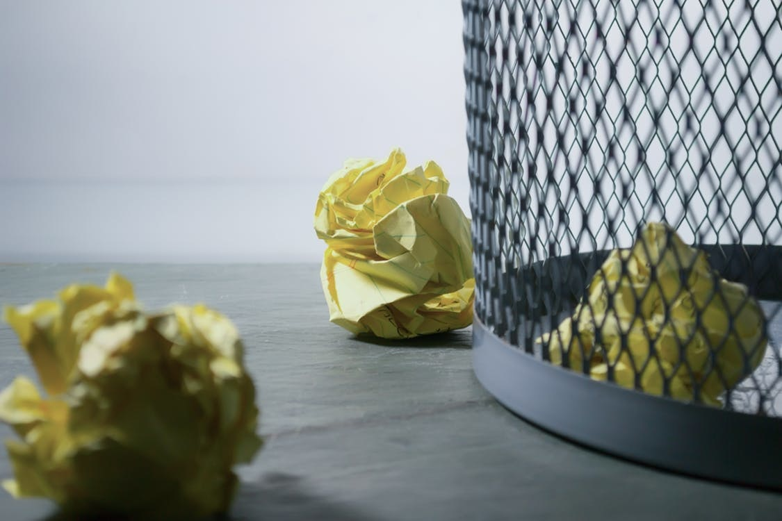 pieces of yellow crumped up paper next to a trash can