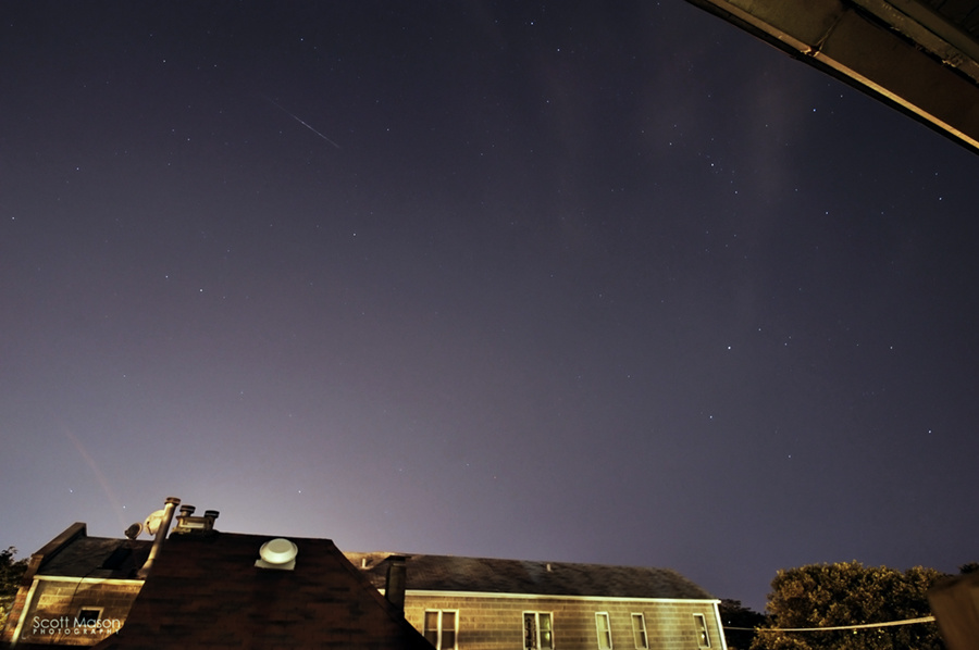 a meteor in the sky above a house in the city