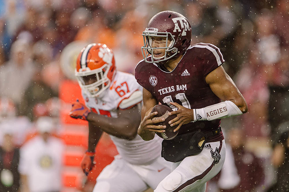 Kellen Mond of Texas A&M runs in the rain against Albert Huggins of Clemson.