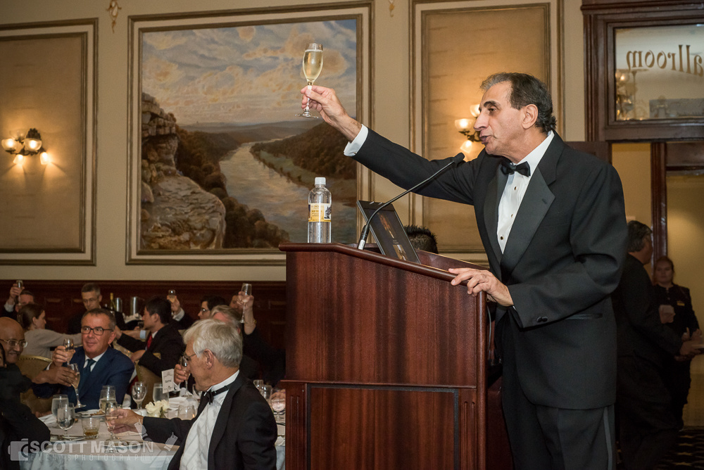 an event photo of a man holding his wine glass out from behind a podium, proposing a toast