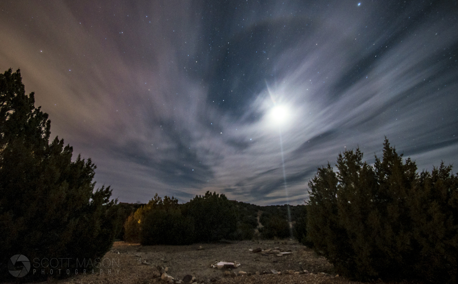 a photo of the moon with a halo around it with a desert landscape below