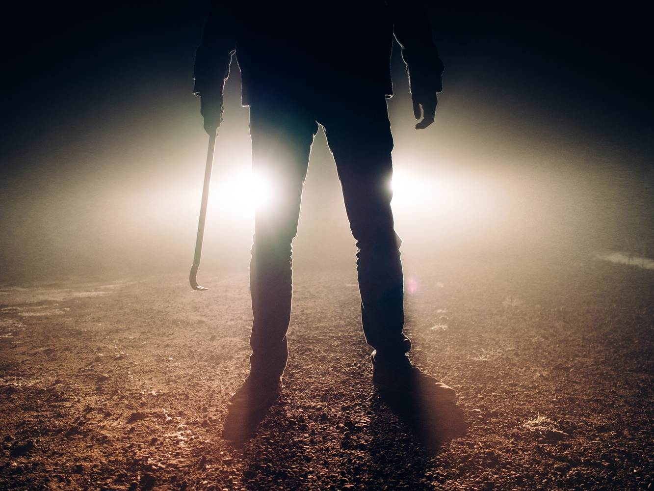 a photo of a man backlit by bright truck headlights holding a crowbar