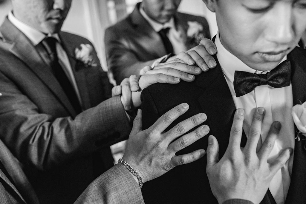 A groom surrounded by groomsmen.