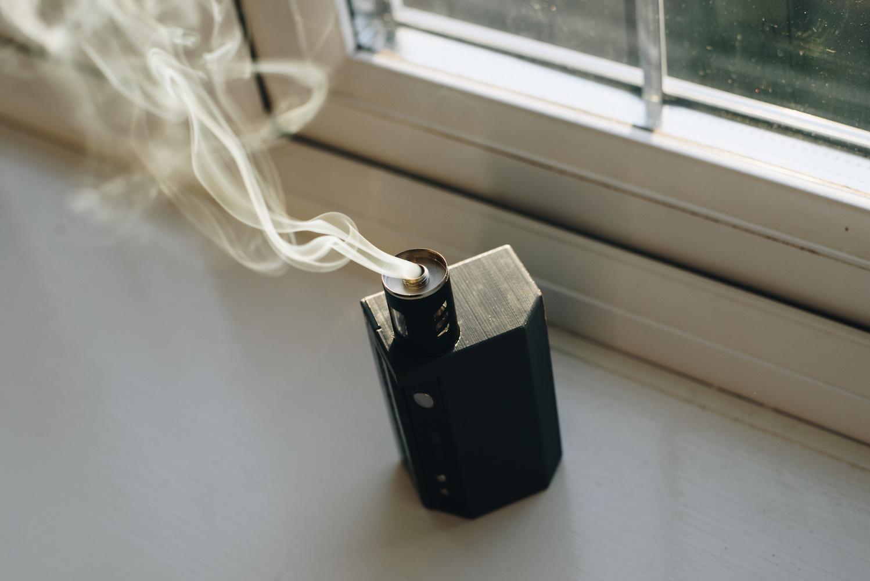 Smoke machine releasing smoke on a windowsill.