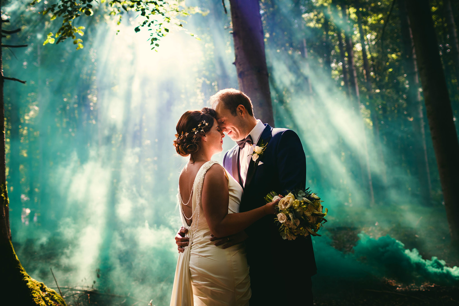 Photograph of a bride and groom in a forest.