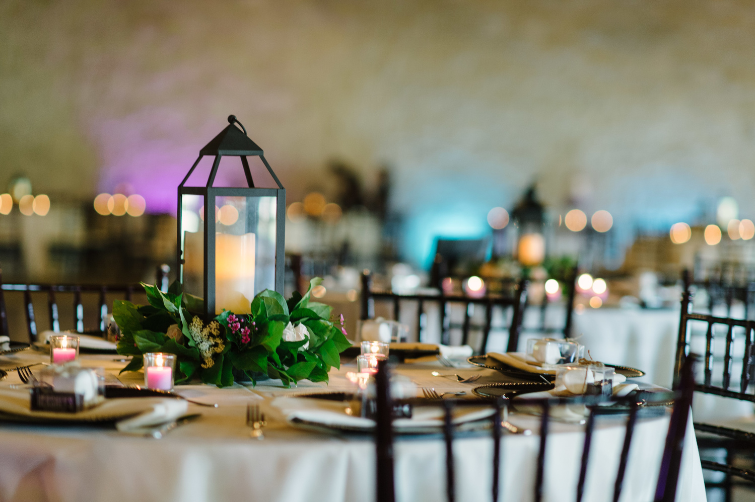 Lights, place settings, center pieces, and candles at a wedding