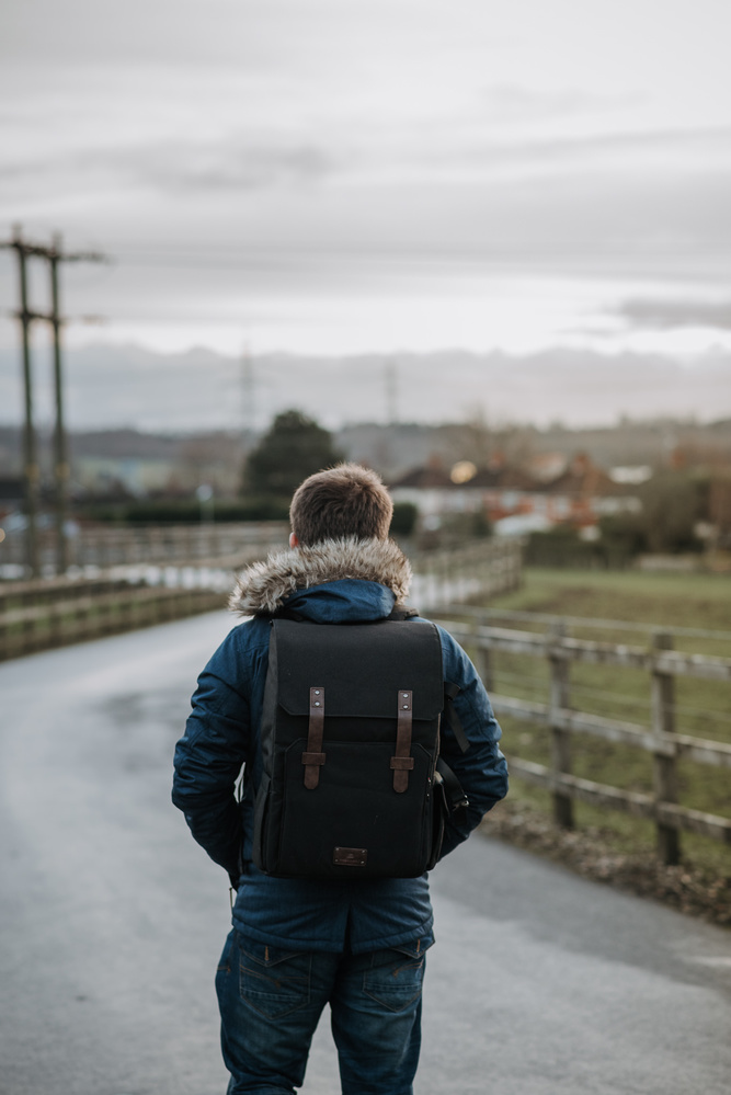 Man with a backpack walking down a country lane
