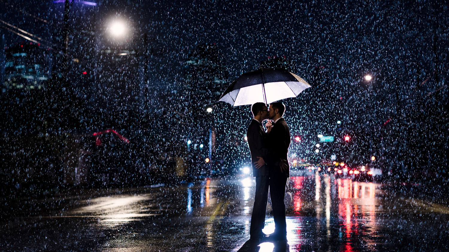 Gay couple kissing in the rain while backlit
