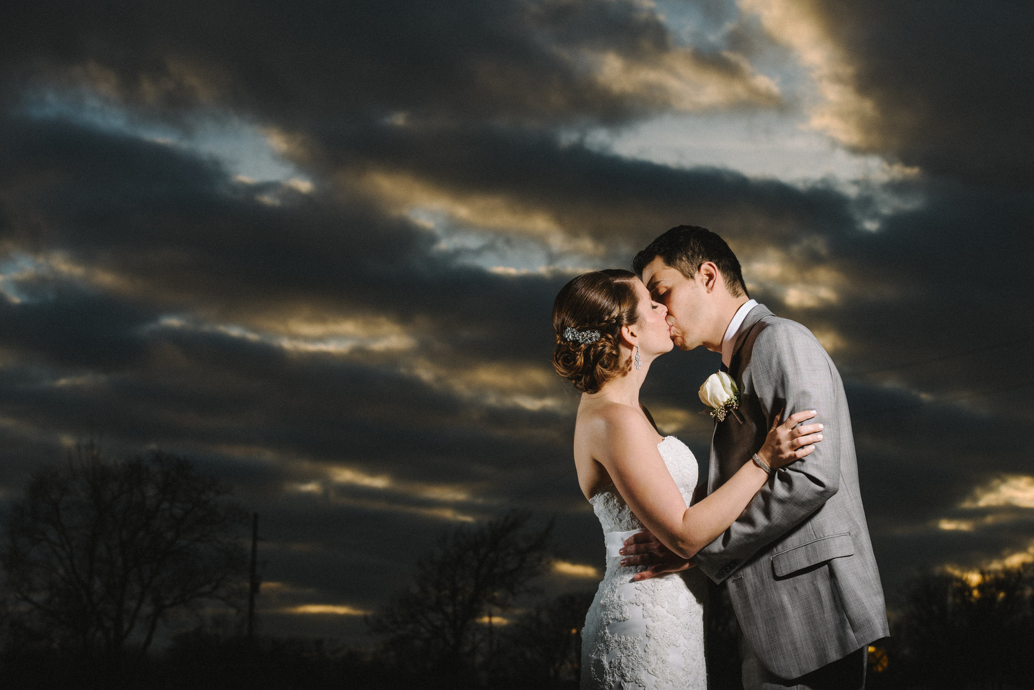 Couple kissing during sunset with dramatic clouds