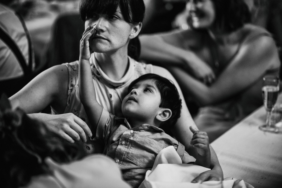 A child playing on his mother's lap at a wedding breakfast